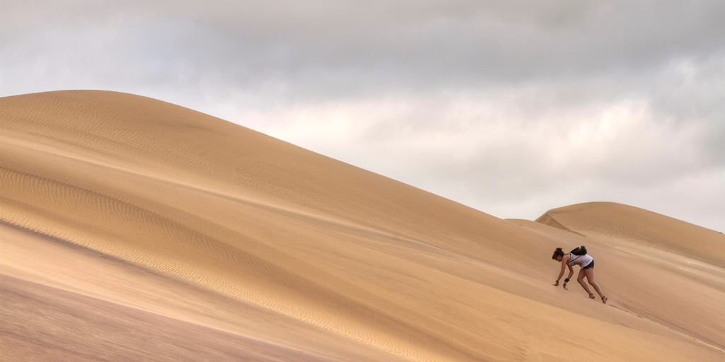 Girl climbing a sand dune in front of overcast sky in Namibia