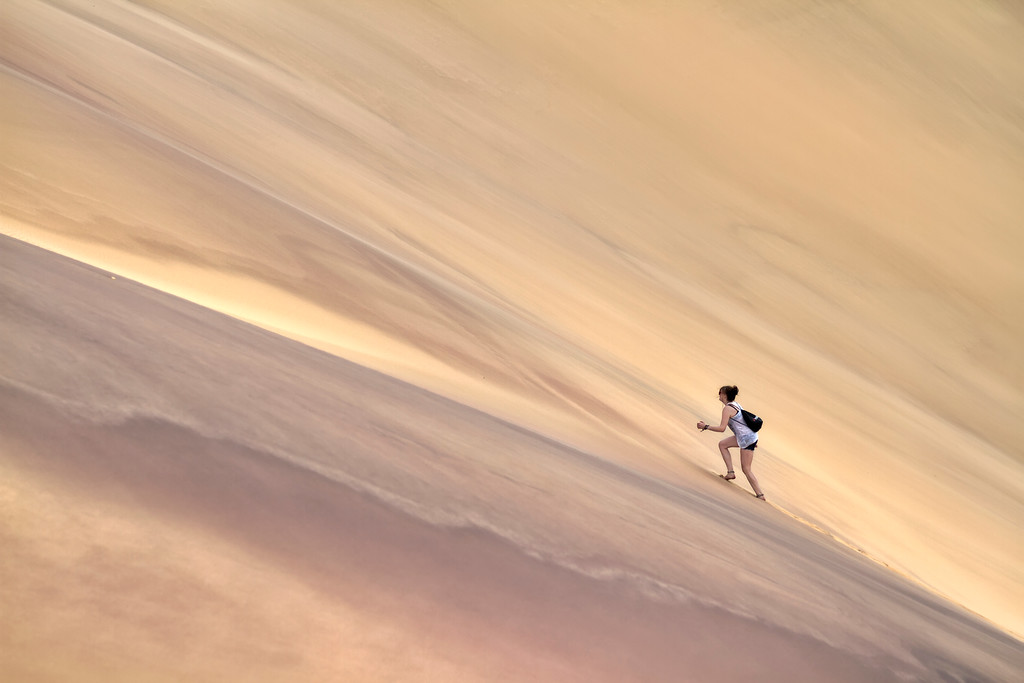 A girl climbing up a steep sand dune at dune 7 in namibia