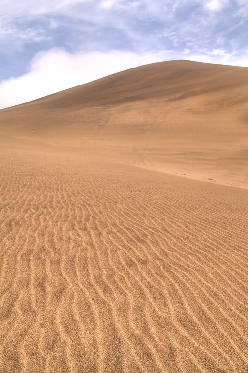 Ripples of sand lead to the back side of Dune 7, Namibia in front of a blue sky with fluffy white clouds