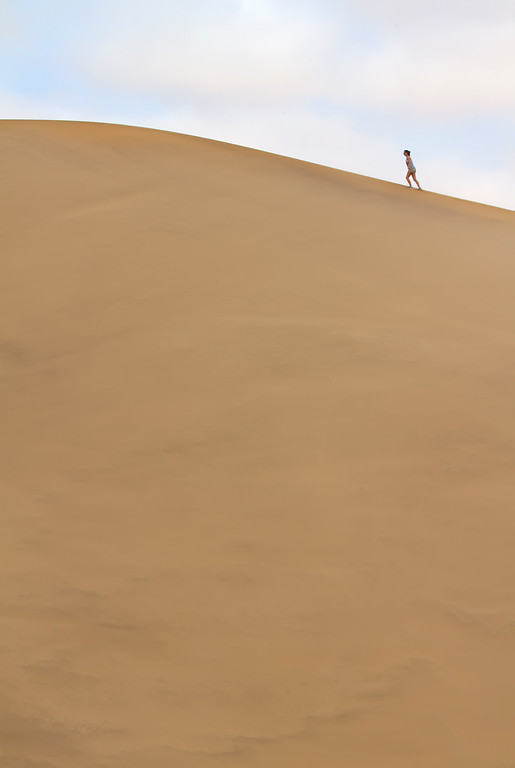 A girl walking near the top of a giant sand dune at dune 7 in Namibia