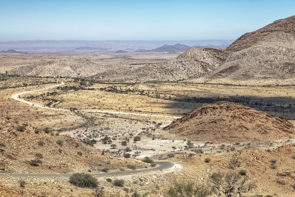 The desert of Namibia taken from atop a hill with winding dirt roads in the foreground.