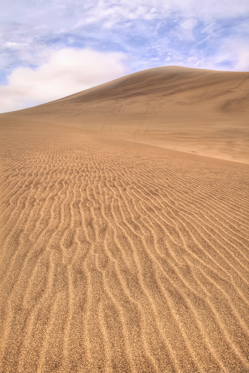 Ripples in the sand lead to a view of the backside of dune 7 namibia in front of a partly cloudy blue sky
