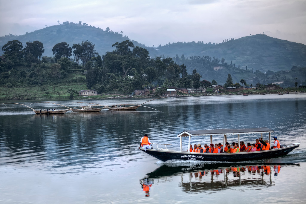 On Lake Kivu, local fishermen and tour boat with tourists in orange life-jackets and Rwanda's rolling green hills beyond.