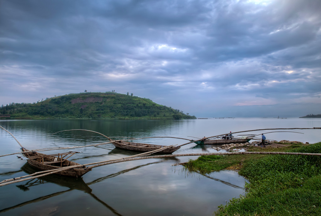 Triple fishing canoes used on Lake Kivu, Rwanda under a stormy sky with the rest of the fleet seen on the horizon.