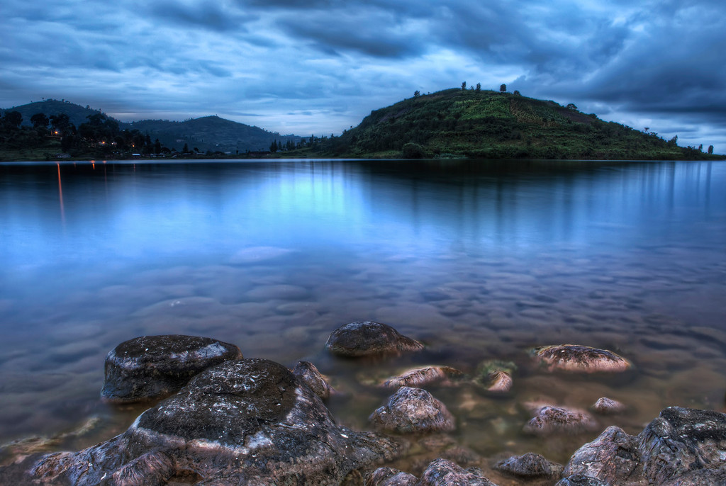 The blue hour before dawn on Lake Kivu at Paradis Malahidein Rwanda under an overcast sky with calm water and green hills across.