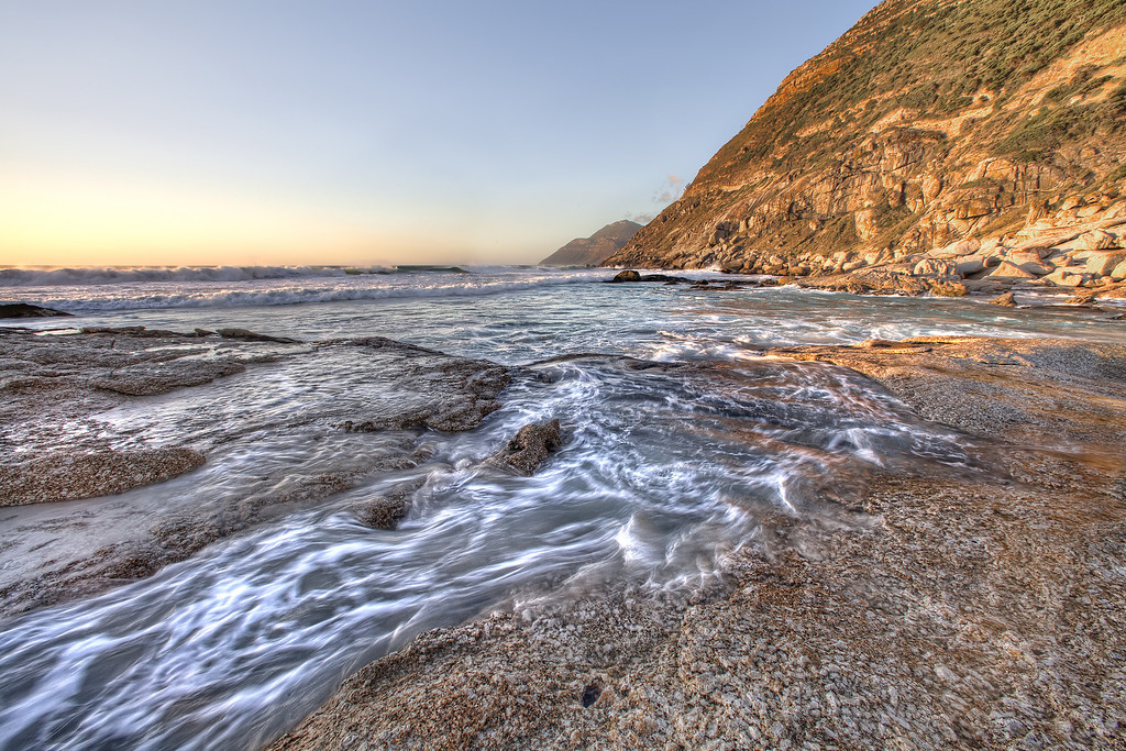 Ocean swirling over rocks at Nordhoek Beach Cliffs, South Africa