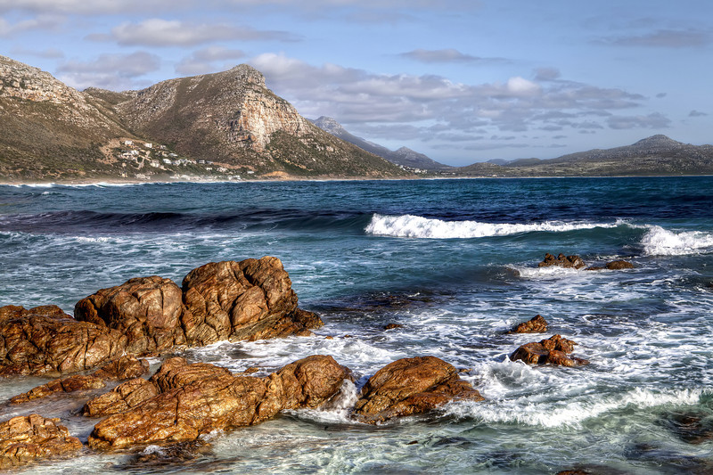 Witwatersands beach cape town south africa with boulders in the water and mountains in the background.