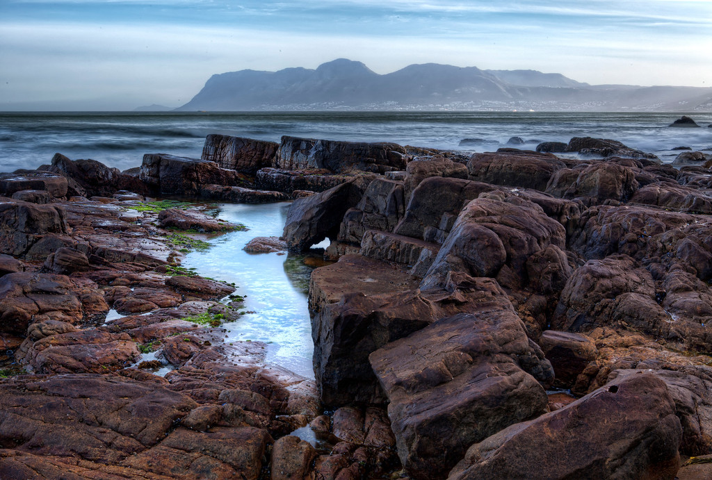 Rugged, rocky coast of False Bay, South Africa with cliffs across the water.