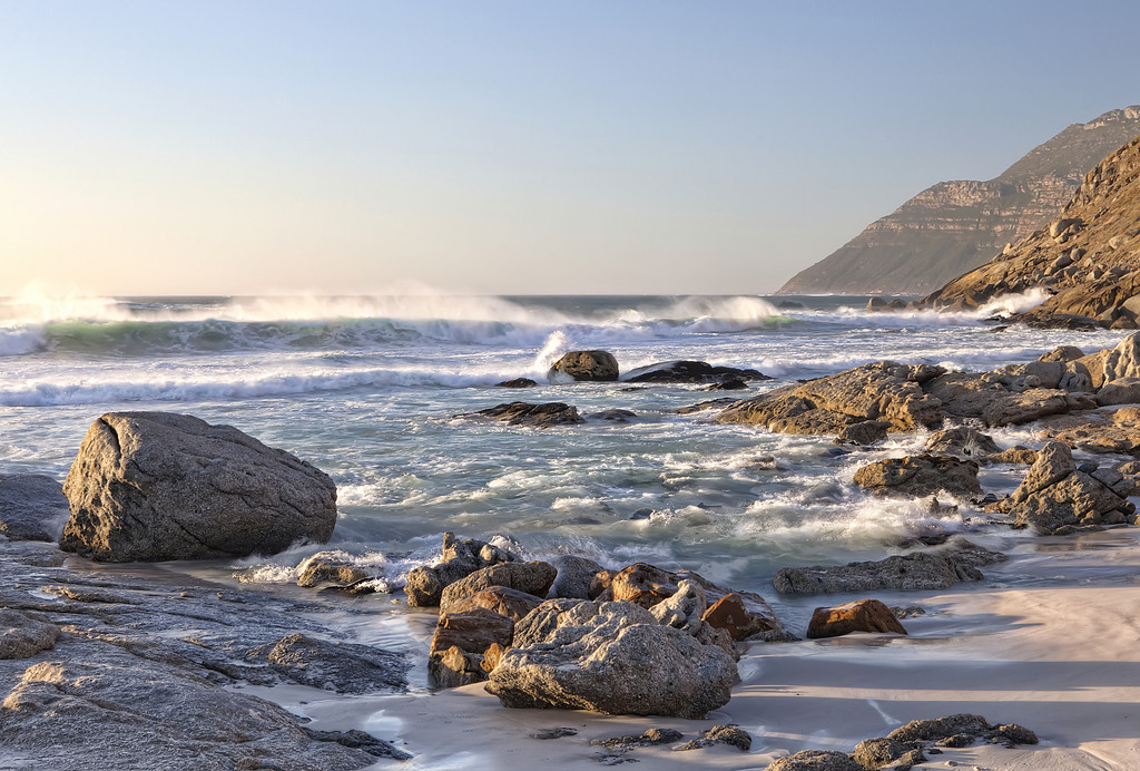 Powerful waves hitting the rocks on Nordhoek Beach in Cape Town with a rugged coastline under the setting sun.