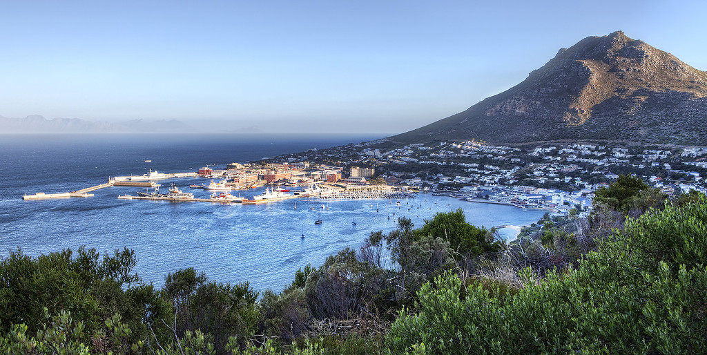 View of old naval port of Simonstown, South Africa at sunset with mountain in background.