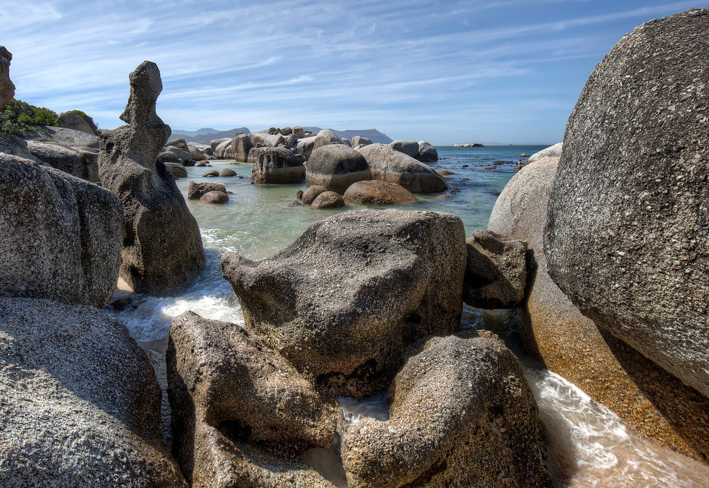 Boulders Bay, South Africa showing rocks carved by the elements in the ocean including one tall skinny one.