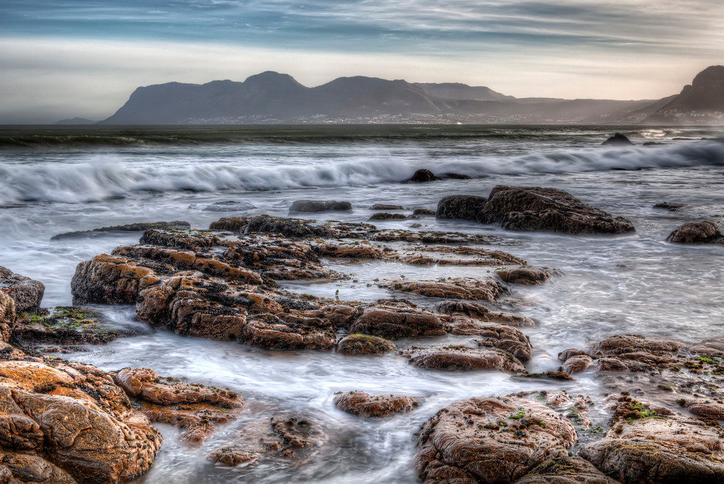 Rocks on the rugged coast of False Bay, South Africa with view across the bay of Simons Town.