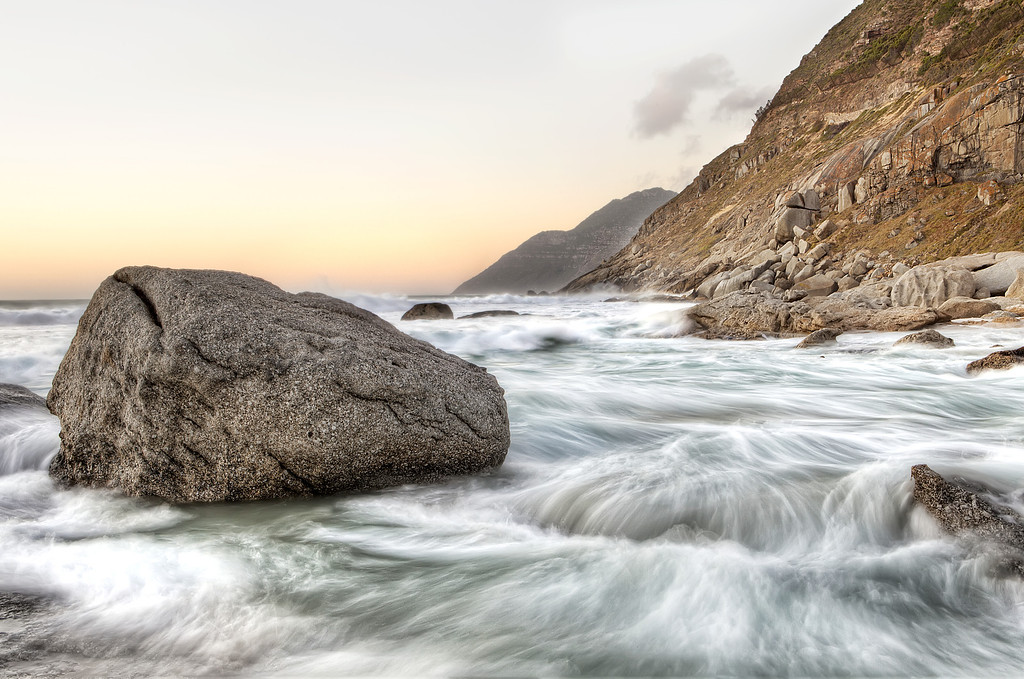 Whitewater rushes around a boulder on the rocky area of Nordhoek Beach, Cape Town, South Africa