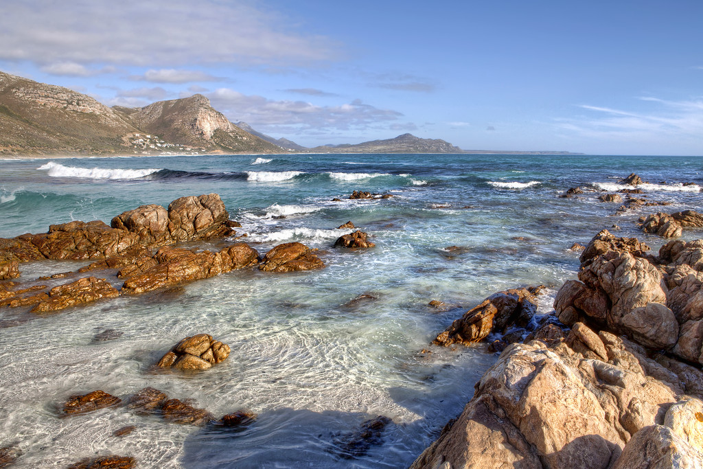 A view of Witwatersounds beach in Scarborough in South Africa with rocks in the foreground and mountains and blue sky in the background
