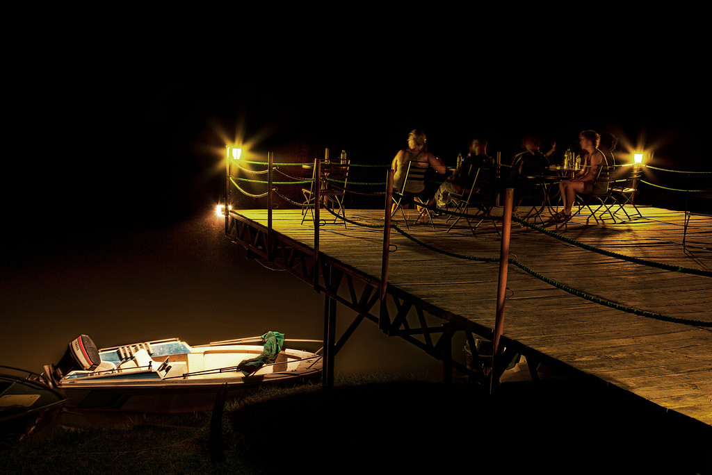 Safari-bound at Zambezi Breezers, sitting on the wood deck over the Lower Zambezi in the night with golden lights in Zambia.