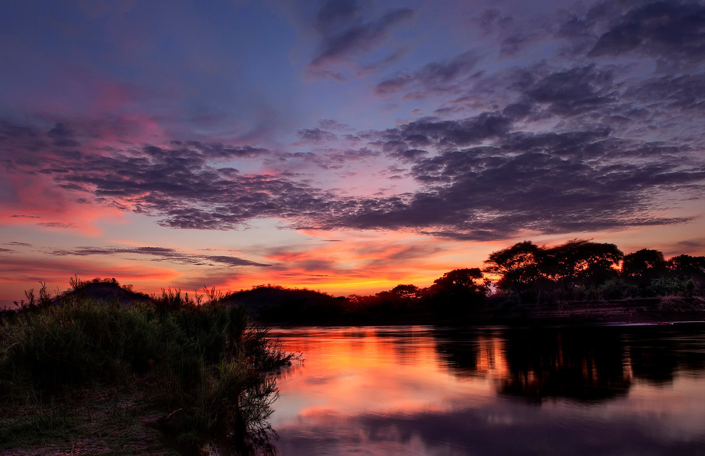 Fiery sunrise with land and trees in silhouette reflected in the Lower Zambezi River in Zambia