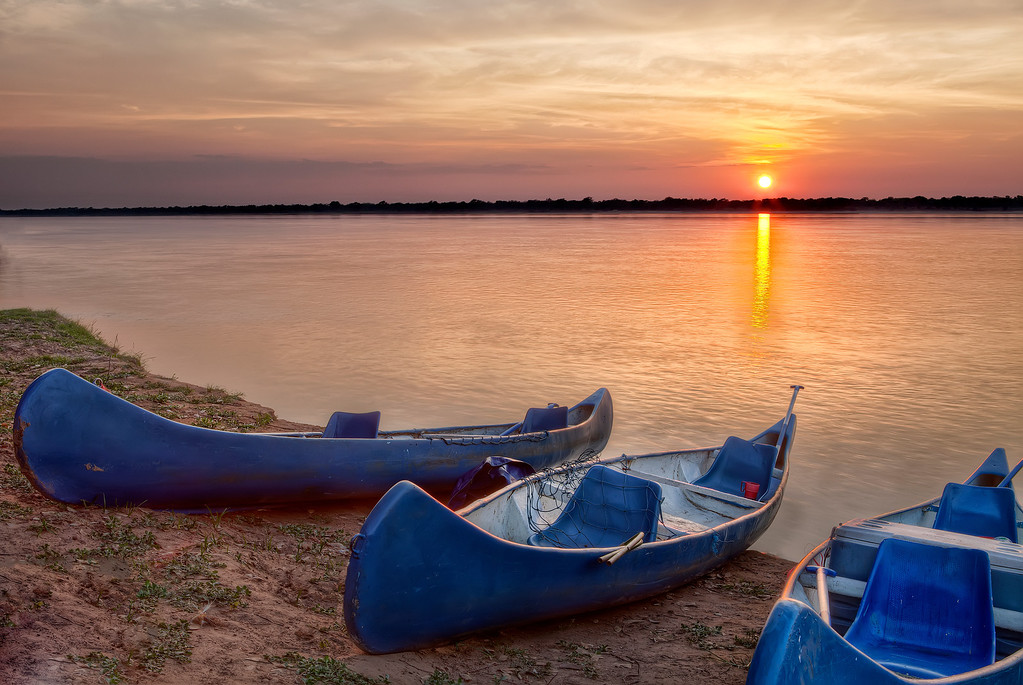 Three blue canoes on the Zambezi riverside with an orange sun rising over the horizon leaving orange streaks on the water in Zambia.