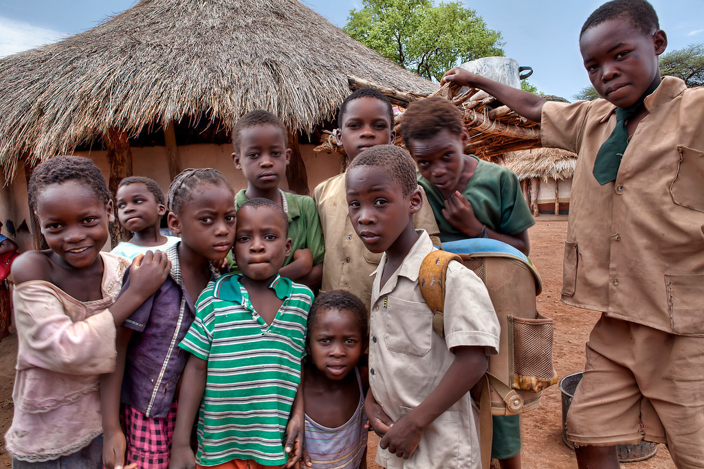 Candid photo of village children in front of a round straw roofed hut in Zambia