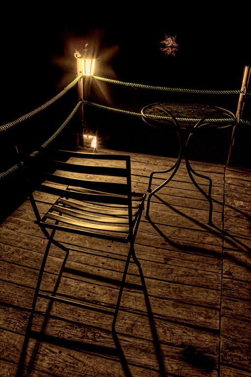 Empty chair and table on the deck in the black of night lit by a lantern overlooking the Zambezi River in Zambia