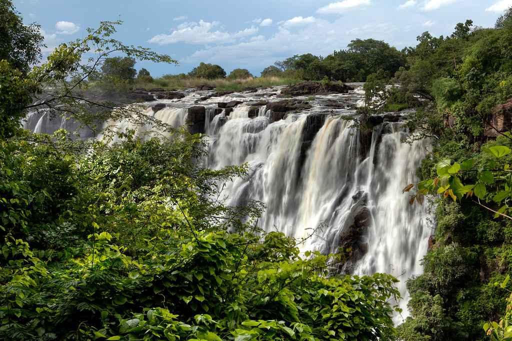 The Victoria Falls at high water framed by surrounding lush green plantlife