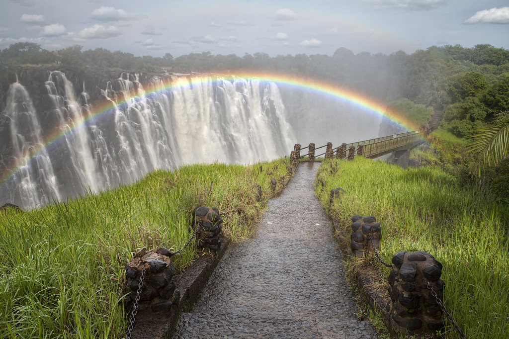 A rainbow arcs across Victoria Falls and the Livingstone bridge at high water in Zambia