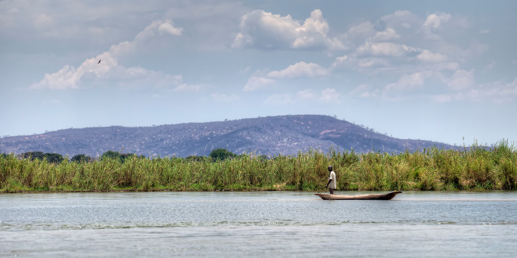 Standing fisherman in a dugout canoe on the lower Zambezi river in  Zambia with vegetation and hills in the background