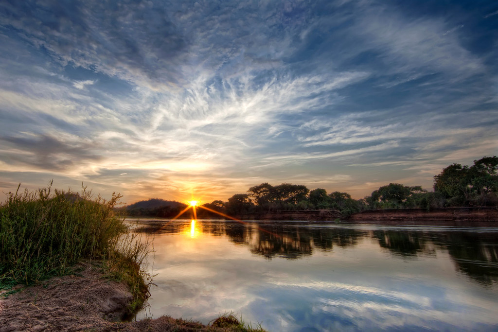 Glorious star-burst sunrise peeking over the horizon on the Zambezi River in Zambia.