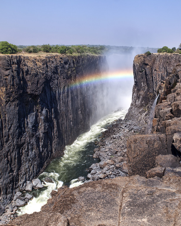 View of the Victoria Falls, Zamabia during the dry season with a torrent of water and a rainbow between the gorge.