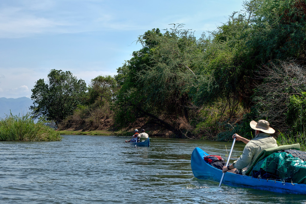 Two canoes floating through a narrow channel of the Zambezi River on safari in Zambia