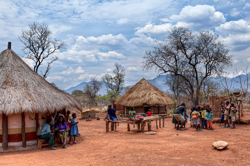 Village with round straw huts in Rwanda with groups of local children posing for a photo while others learn to use the camera, under a beautiful blue sky with clouds.