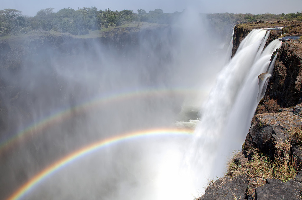 A double rainbow in the mist of the Victoria Falls waterfall in Zambia