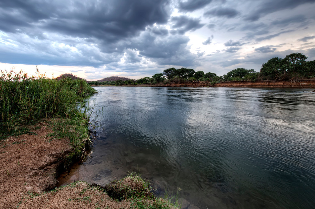 Zambezi River in Zambia with wind blowing across it creating texture on the surface of the water with dark dramatic clouds above.