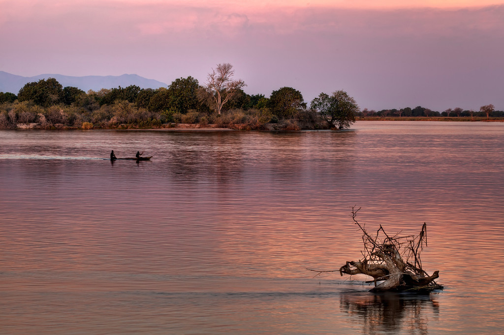 Sunset on the Lower Zambezi River, Zambia with local men in simple canoe riding with back end in the water.