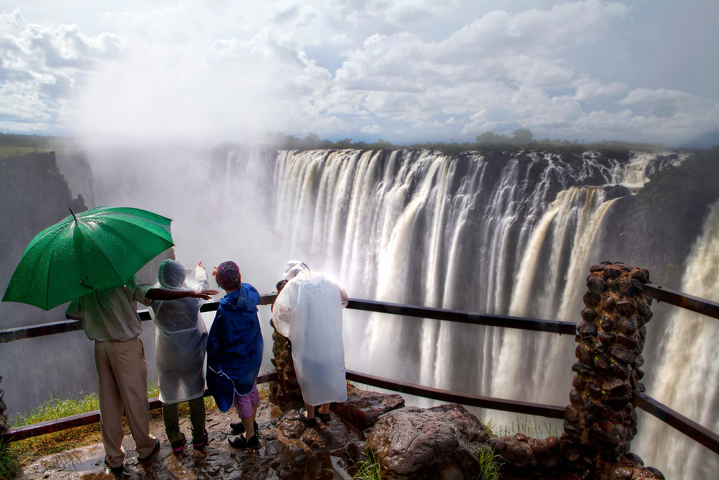 Four tourists in ponchos view the Victoria Falls waterfall in the Batoka Gorge surrounded by swirling mist