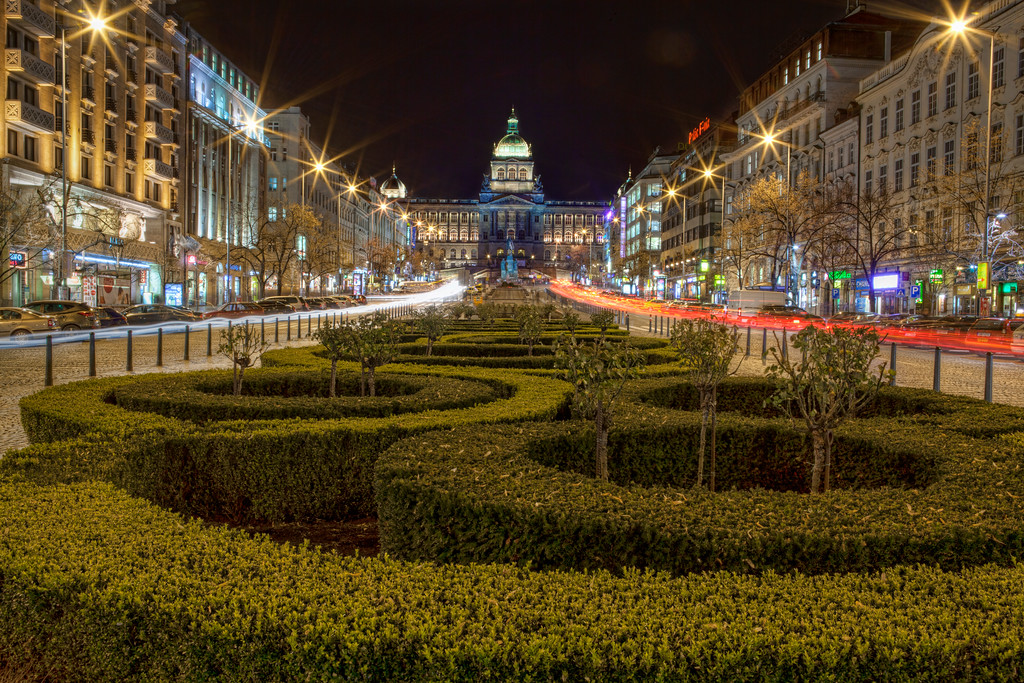 Wenceslas Square, Prague lit up at night with circular hedges in foreground.