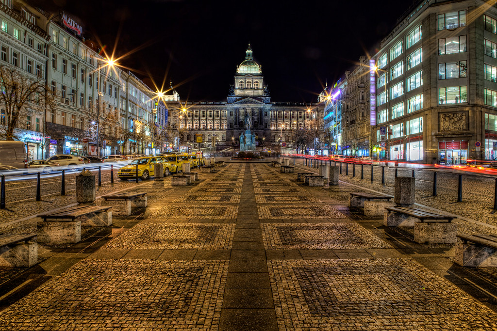 Wenceslas Square in Prague lit up at night with symetrical cobblestones in the foreground.