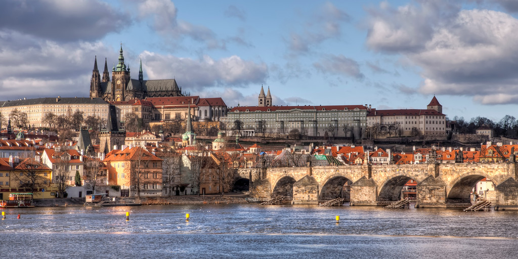 Panoramic view of Vitus Cathedral, Prague Castle, and Charles Bridge in Prague from across the Charles River.