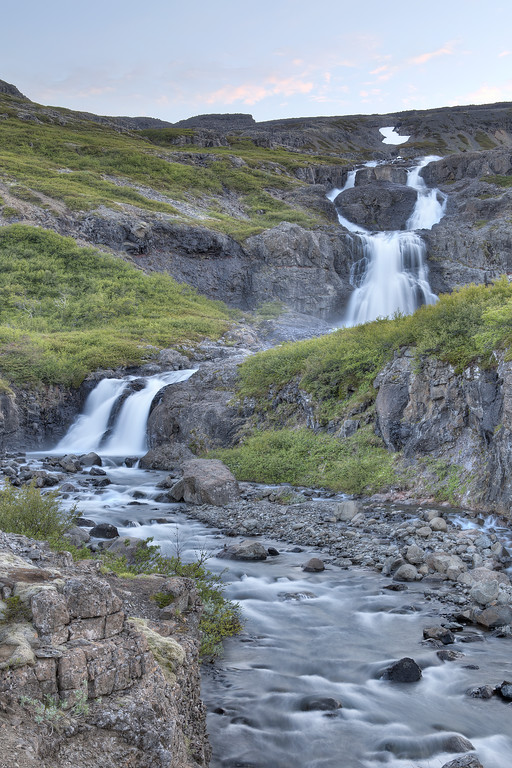 Waterfall meandering down the green covered rocky hills to a stream in Westfjords Iceland