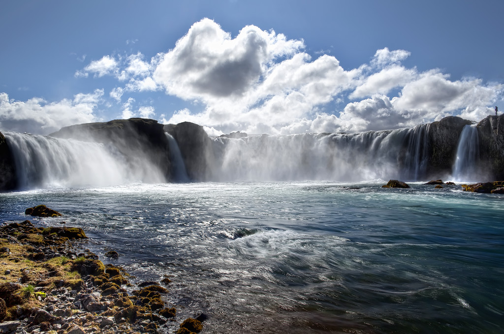 View from below the mighty Godafoss waterfall in Northern Iceland under a blue sky where the river water looks turquoise.