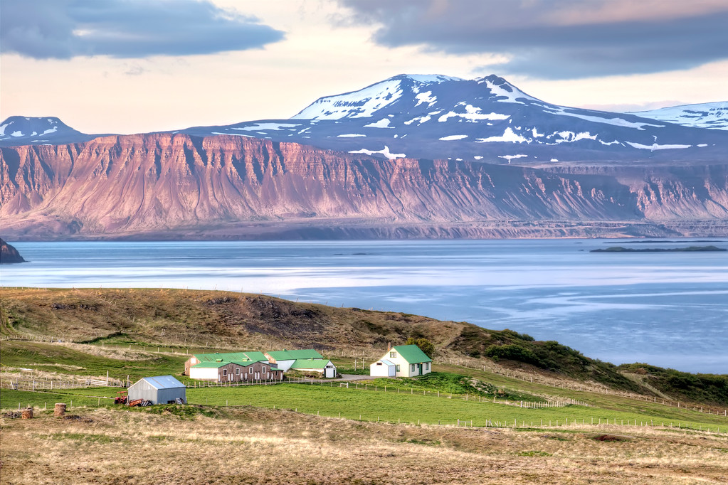 Farm with green roofed buildings, ocean. and snow topped mountains in Westfjords, Iceland.