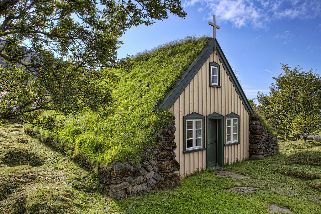 A church with a roof made of turf grass in Hof, Iceland in front of a blue sky