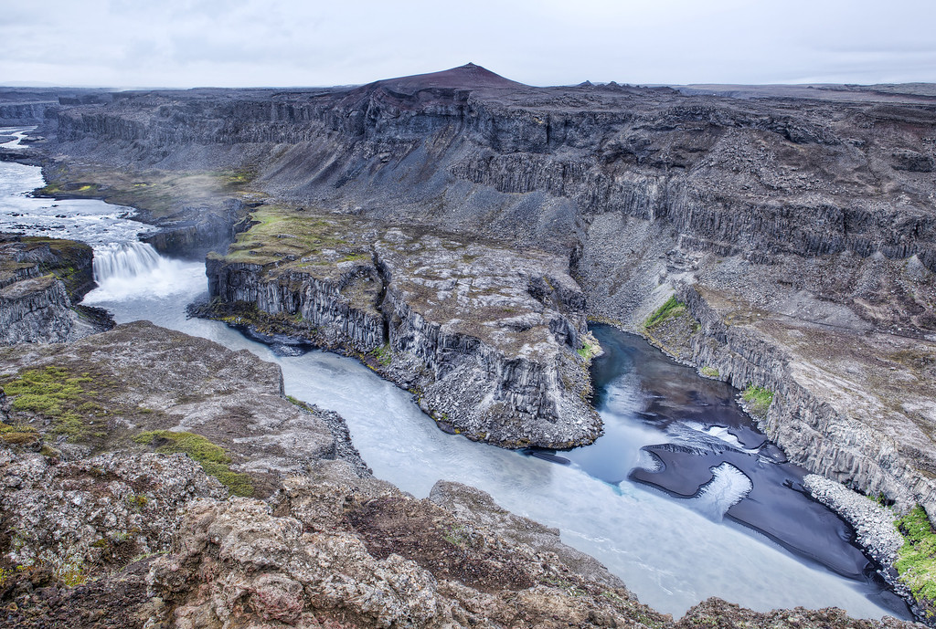 View from the crest of the cliffs overlooking Hafragilfosswaterfall in Iceland is of a rugged landscape with a gorge bore out by flowing water with the mist of Dettifoss seen rising into the sky just around the bend up river.