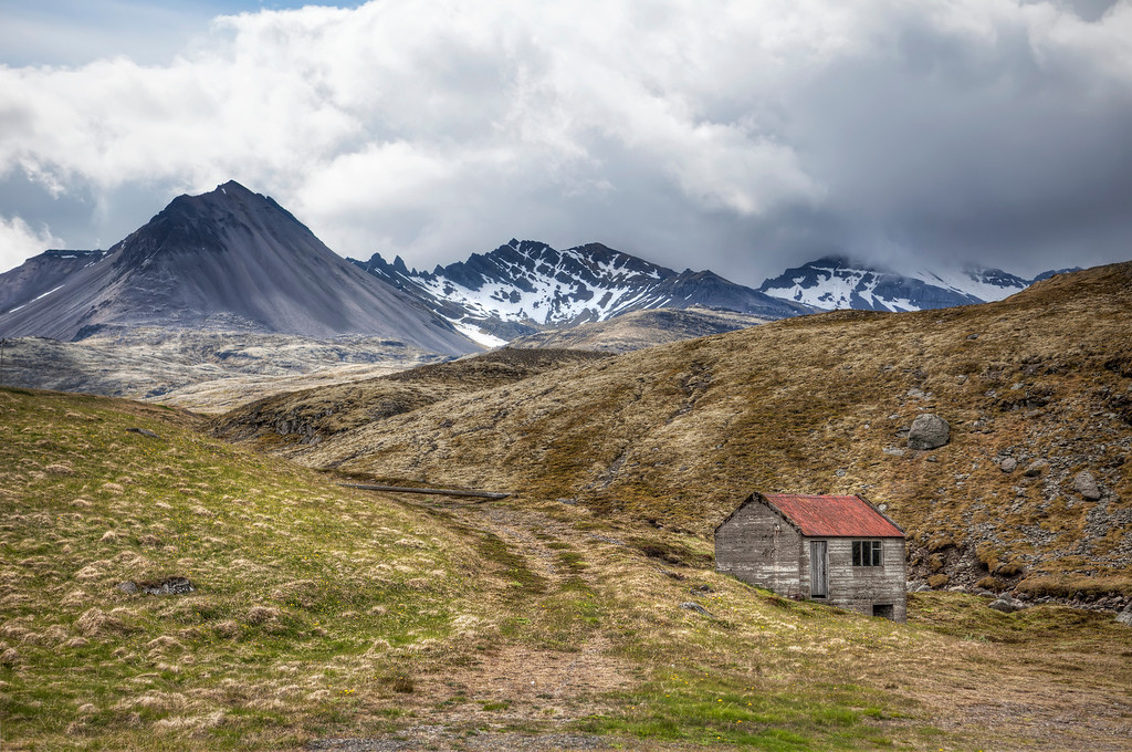 Lonely wood shack with majestic snow covered mountains with storm clouds in East-fjords, Iceland.