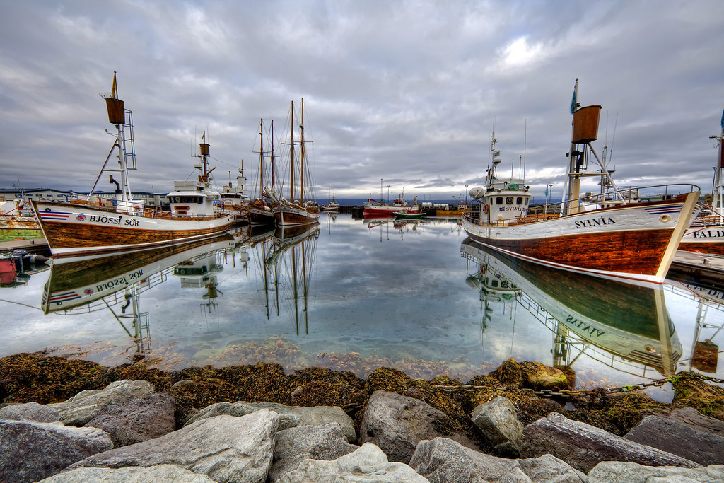 Marina in Husavik, Iceland with old fashioned wooden boats which reflect in the water where they are docked.
