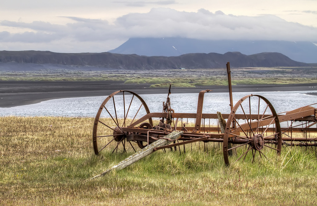 Old rusted horse-drawn rake on a farm in front of a mountain in Iceland