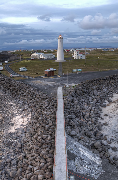 The new lighthouse at Gardur, Iceland with straight path and rocks leading to it.