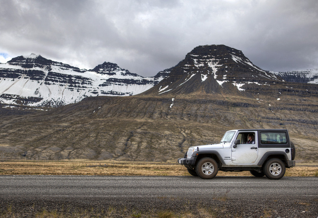 White jeep on the road in front of snow covered mountains with a grey sky in the East Fjord region of Iceland