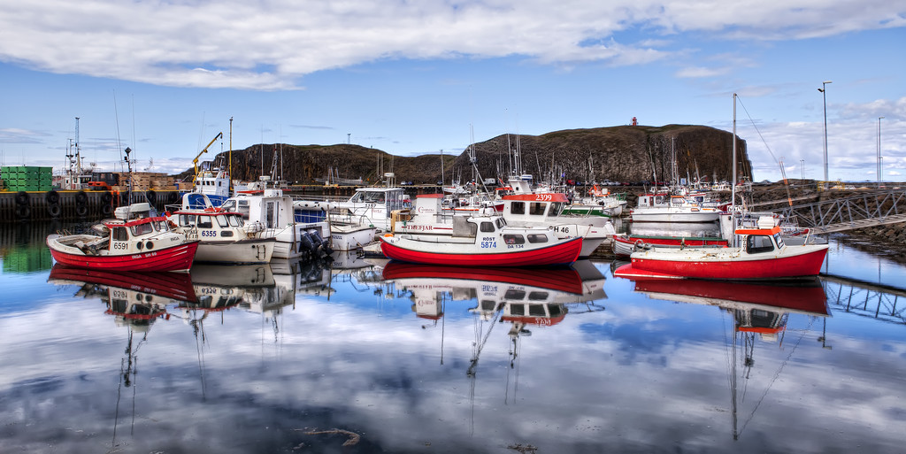 Three red boats in a harbor with water reflections of the boats and blue sky with clouds in Stykkisholmur Iceland