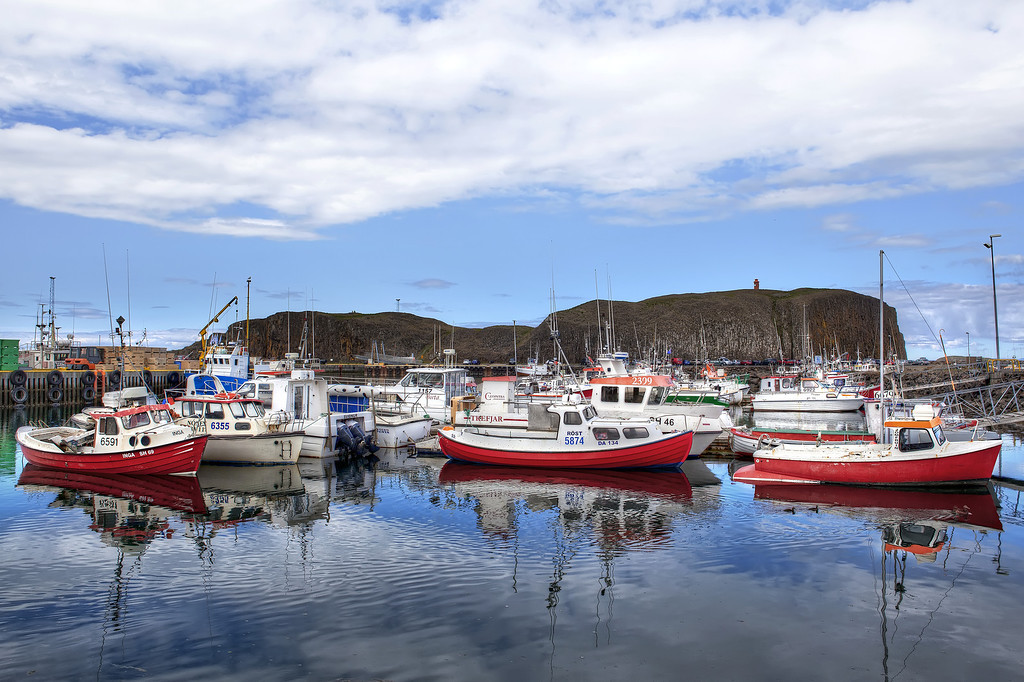 Red boats with others with a blue sky and calm water docked in a old fishing village in Stykkishólmur, Iceland