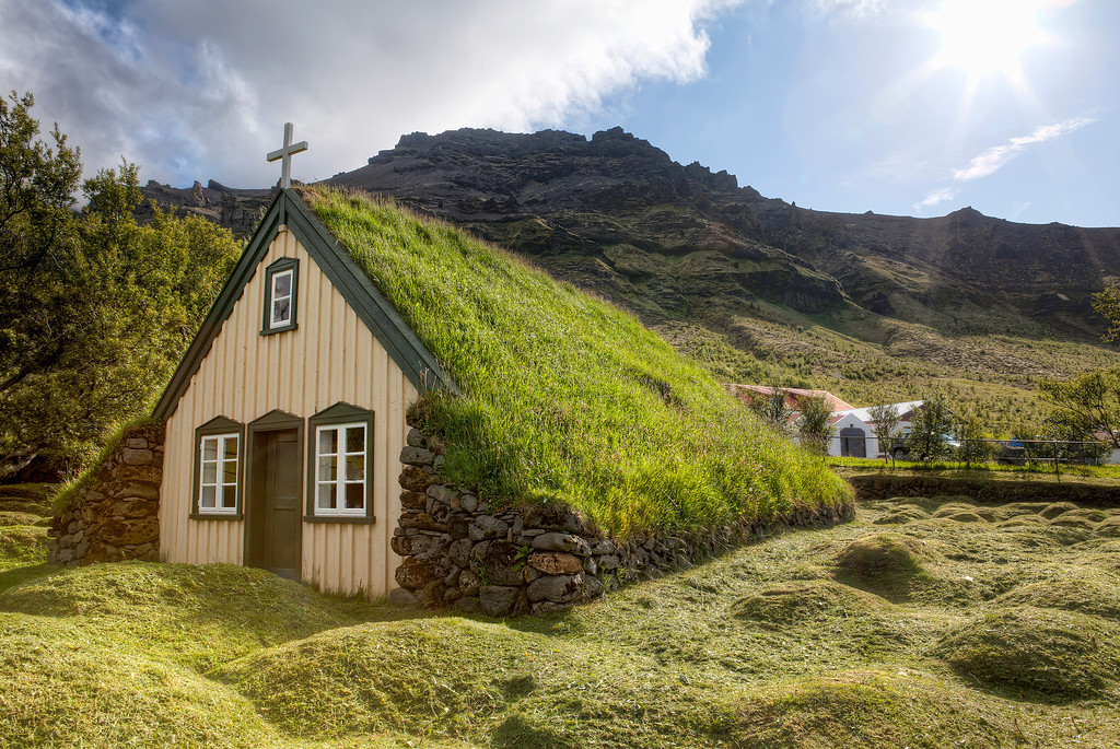 Turf covered church with only the beige plank front showing while being surrounded by rolling green in Skaftafell, Iceland.